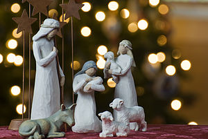 A depiction of the birth of Jesus with a Christmas tree backdrop.